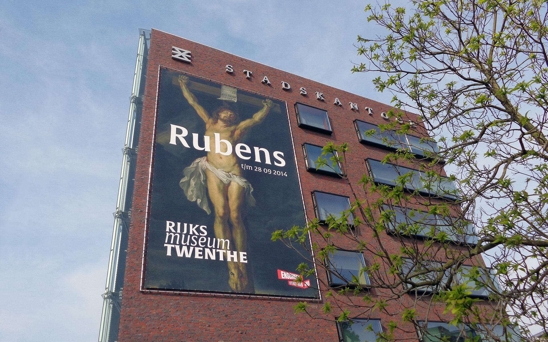 Hier zie je de gevel van het Stadskantoor te Enschede, waar wij een grote banner hebben gemonteerd in een buizenframe met de opdruk van Jezus. ter promotie van de tentoonstelling met de meesterwerken van Rubens, Van Dyck en Jordaens - de Vlaamse barok die te bezichtigen is tot en met 28 september 2014 in het Rijksmuseum Twenthe te Enschede | Mondice